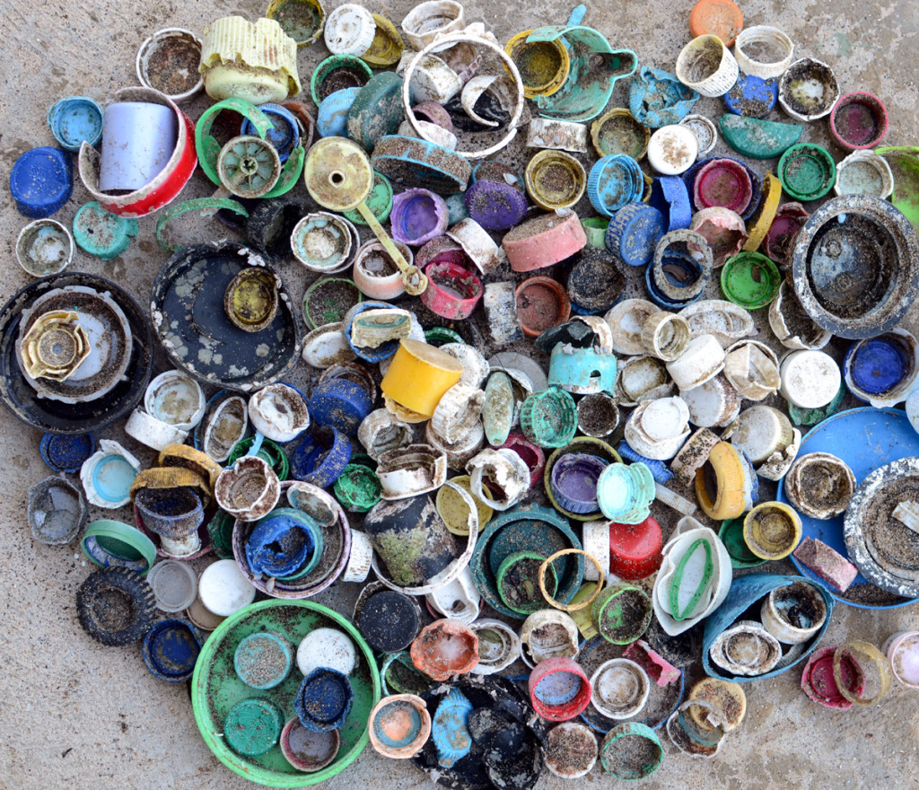 A collection of plastic bottle caps and lids from the high water line of Wainiha Beach, Kauai, Hawaii.